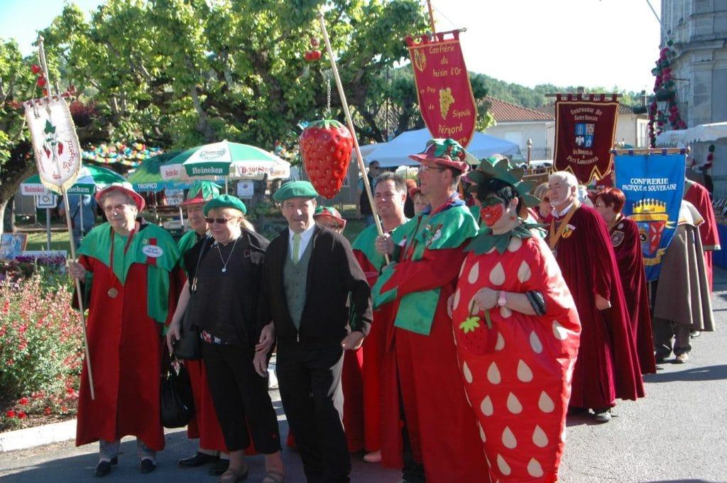 Fête de la fraise à Vergt avec le défilé des gens déguisés de la confrérie de la fraise